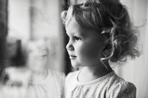 Zwart-wit portret van kinderen meisje kijkt door raam.