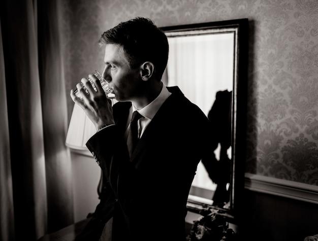 Zwart-wit portret van knappe jonge man in kamer drinken gekleed in pak
