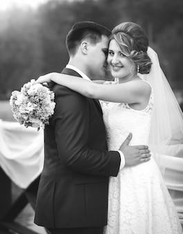 Zwart-wit portret van knuffelende en lachende bruid en bruidegom in het park