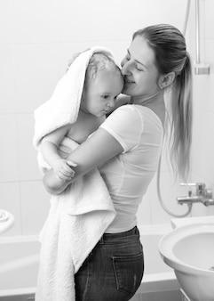 Zwart-wit portret van schattige babyjongen die moeder knuffelt na het baden