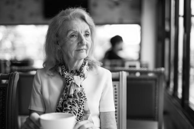 Zwart-wit portret van senior oudere vrouw koffie drinken