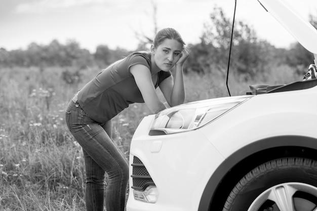 Zwart-wit portret van trieste vrouw die op kapotte auto kijkt op het platteland