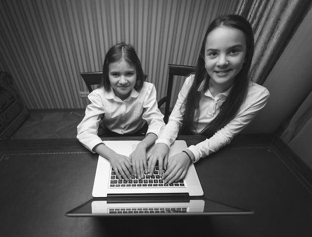Zwart-wit portret van twee tienermeisjes die laptop gebruiken bij kabinet
