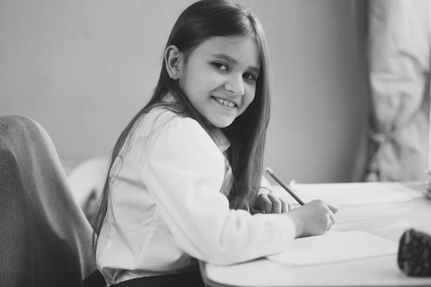 Zwart-wit portret van vrolijk meisje huiswerk