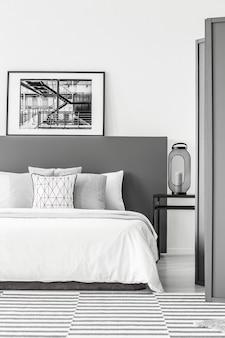 Zwart-wit poster op bedhoofd van bed in eenvoudig slaapkamerinterieur met lantaarn op een nachtkastje