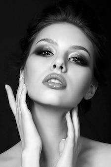 Zwart-wit schoonheidsportret van jonge vrouw wat betreft haar gezicht. zwart-wit foto.