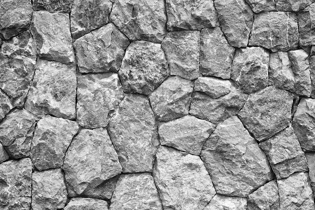 Zwart-wit schot van de textuurachtergrond van de steenmuur
