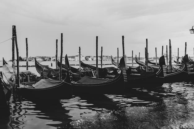 Zwart-wit schot van gondels aangemeerd in het water