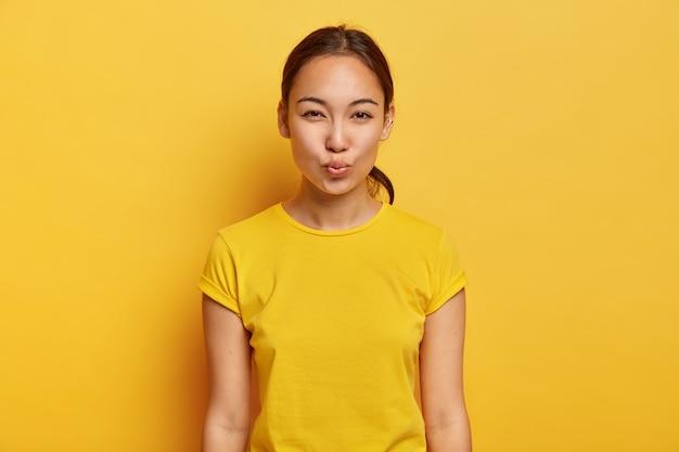 Zwart-wit shot van mooie vrouw met aziatische uitstraling, gezonde huid, piercing in het oor, houdt de lippen gevouwen, wacht op een kus, heeft een flirterige bui, draagt een gele casual t-shirt. gezichtsuitdrukkingen concept