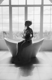 Zwart-wit silhouet van een bruid in een trouwjurk in een luxe interieur met ligbad
