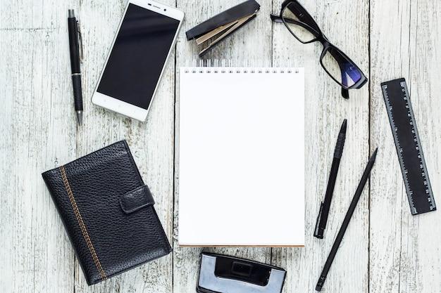 Zwart-wit stilleven: geopend blocnote, notitieboekjes, pen, potlood, bril, tas.