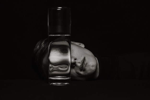 Zwart-wit surrealistisch portret van een man door het glas van een blikje water