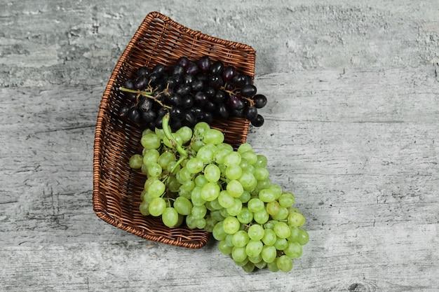 Zwart-wit verse druiven in houten mand.
