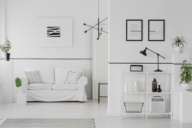 Zwart-wit woonkamerinterieur met comfortabele bank, kussens met patronen, eenvoudige posters en groene planten
