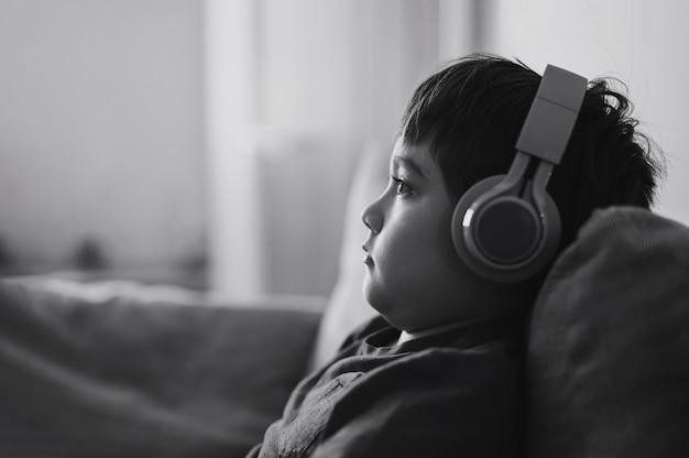 Zwart-wit zijaanzicht portret kind jongen hoofdtelefoon dragen en kijken diep in gedachten, schooljongen in blauw t-shirt luisteren naar muziek, schattige jongen zittend op de bank ontspannen in de woonkamer thuis