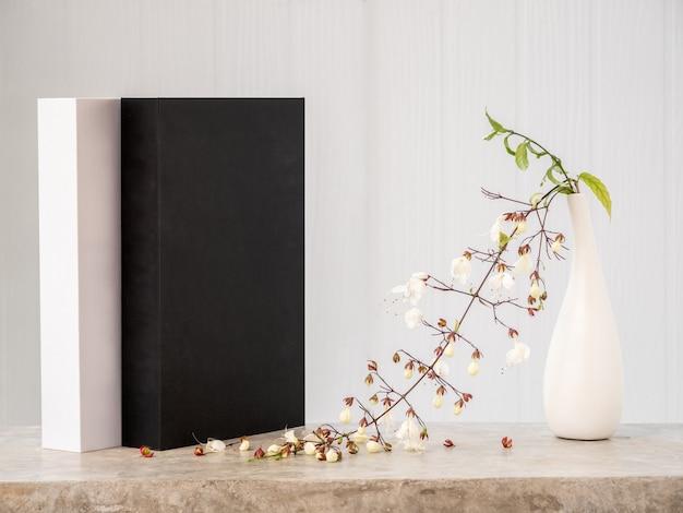 Zwart-witboeken mock-up en mooie knikkende clerodendronbloem in moderne vaas op betonnen tafel