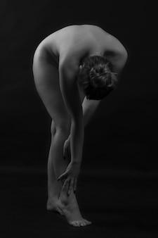Zwart-witfoto van een naakte vrouw die op haar hurken zit