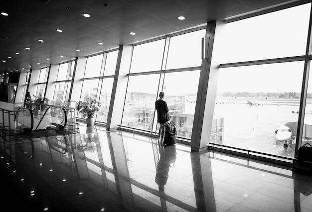 Zwart-witfoto van een vrouw die voor een groot panoramisch raam op de luchthaven staat