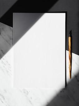 Zwart-witte achtergrond met een witte blanco en een houten kneep gedeeld door schaduwen