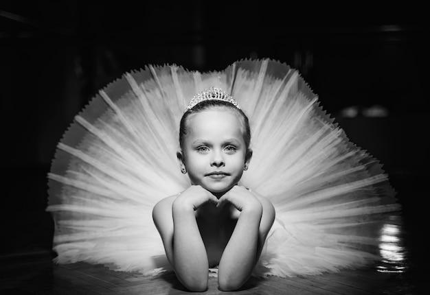 Zwart-witte foto van een leuke glimlachende ballerina in witte tutu en een kroon die op de vloer met handen onder de kin legt.