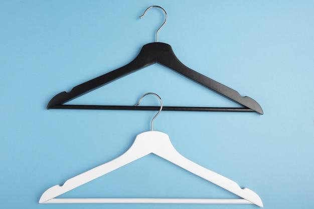 Zwart-witte hangers met elkaar verbonden op blauw. concept weergave.
