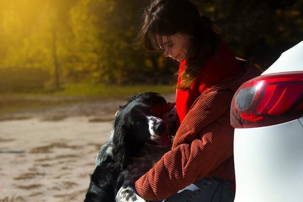 Zwart-witte hond russische spaniël leunt tegen de vrouwelijke meesteres bij de auto op straat