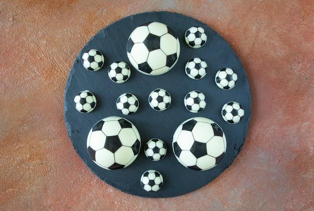 Zwart-witte klassieke voetbalballen op een zwarte ronde serveerschaal - dessertcakes gemaakt van zwarte en witte melkchocolade op de veldachtergrond