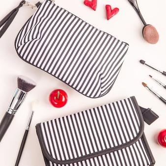 Zwart-witte kosmetische zak onder make-upborstels en heldere rode dingen