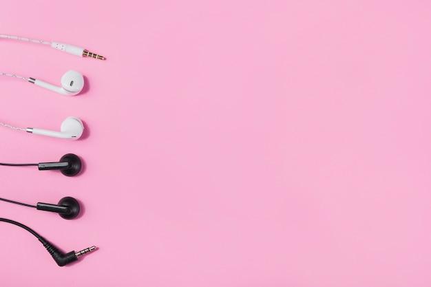 Zwart-witte oortelefoons met plugin op roze achtergrond