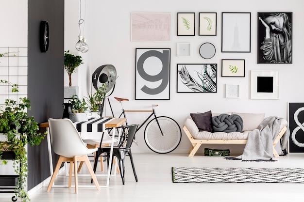 Zwart-witte stoel aan tafel in open ruimte interieur met fiets en posters boven beige bank