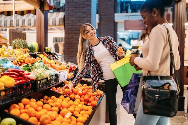 Zwart-witte vrouwen die fruit kopen na het winkelen.
