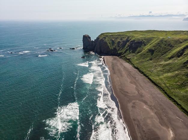 Zwart zandstrand van reynisfjara en de berg reynisfjall vanaf het voorgebergte dyrholaey aan de zuidkust van ijsland.