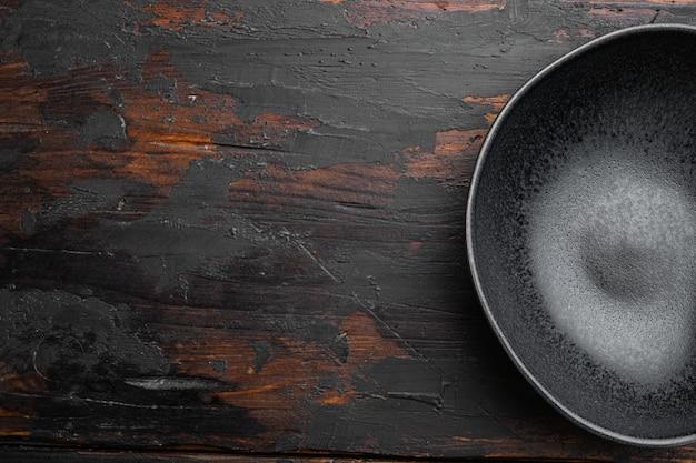 Zwarte aardewerk kom set, met kopie ruimte voor tekst of eten, met kopie ruimte voor tekst of eten, bovenaanzicht plat lag, op oude donkere houten tafel achtergrond