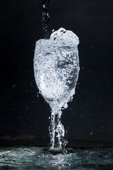 Zwarte achtergrond met overvolle glas water