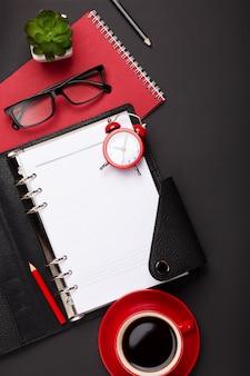 Zwarte achtergrond met rode koffiekopje, kladblok, wekker en bloemen in bovenaanzicht
