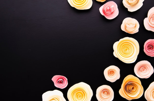 Zwarte achtergrond met schattige papieren bloemen frame en kopie ruimte