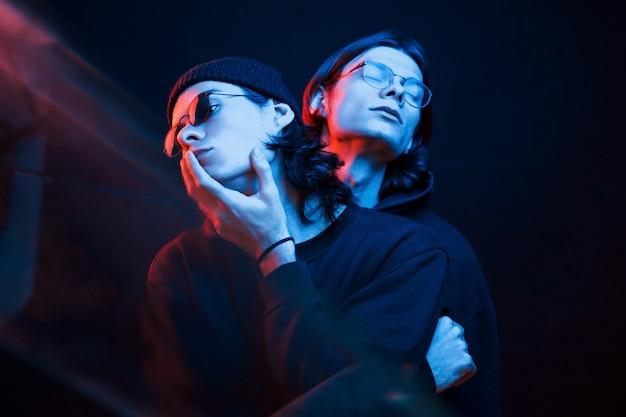 Zwarte achtergrond. portret van tweelingbroers. studio opname in donkere studio met neonlicht
