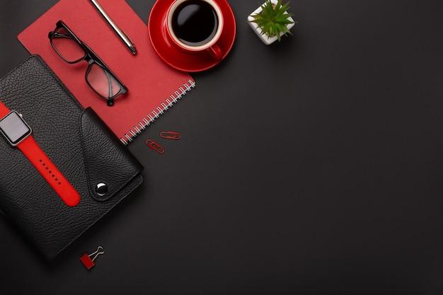 Zwarte achtergrond rode koffiekop notepad wekker bloem dagboek scores toetsenbord op de tafel. bovenaanzicht met kopie ruimte