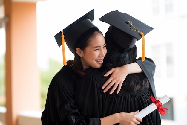 Zwarte afgestudeerden dragen zwarte pakken op afstudeerdag op de universiteit.