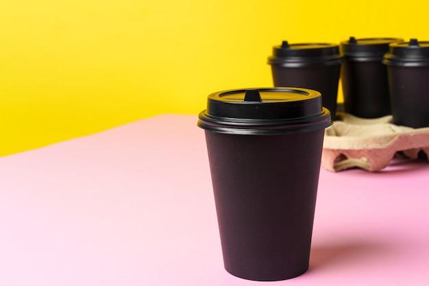 Zwarte afhaalmaaltijden koffiekopjes in houder op tafel