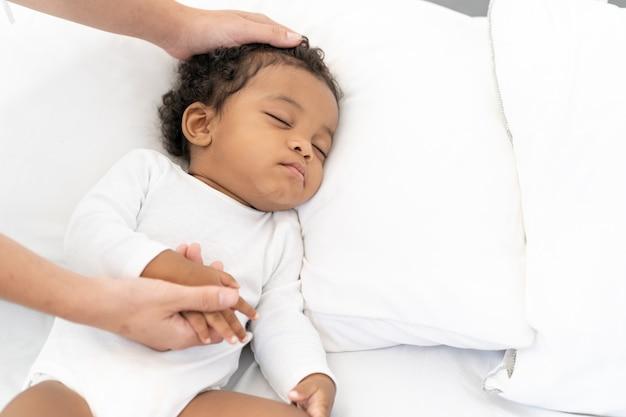Zwarte afrikaanse amerikaanse babyslaap op een witte matras.