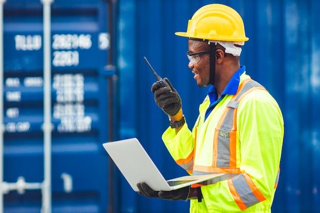 Zwarte afrikaanse gelukkige werknemer die in logistieke communicatie werkt met behulp van radio