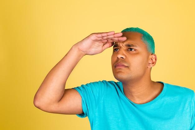 Zwarte afrikaanse man in casual op gele muur kijkt uit in de verte