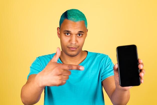 Zwarte afrikaanse man in casual op gele muur met wijsvinger van het mobiele telefoon positieve happy point op zwart leeg scherm