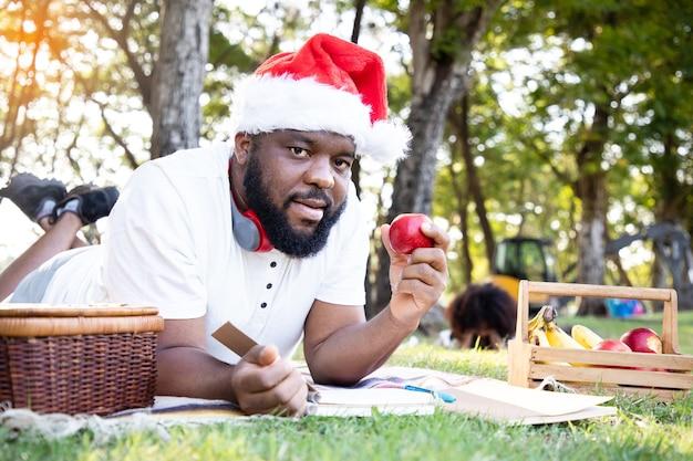 Zwarte afrikaanse man met een kerstman hoed en laptop gebruikt voor communicatie in de tuin