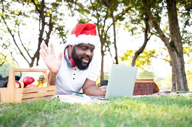 Zwarte afrikaanse man met een kerstman-hoed en laptop gebruikt voor communicatie, werken en hallo zeggen met zijn vrienden in de openbare tuin het gebruik van de natuur helpt om verbeeldingskracht en