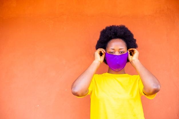 Zwarte afrikaanse vrouw die gezichtsmasker draagt dat zich buiten bevindt