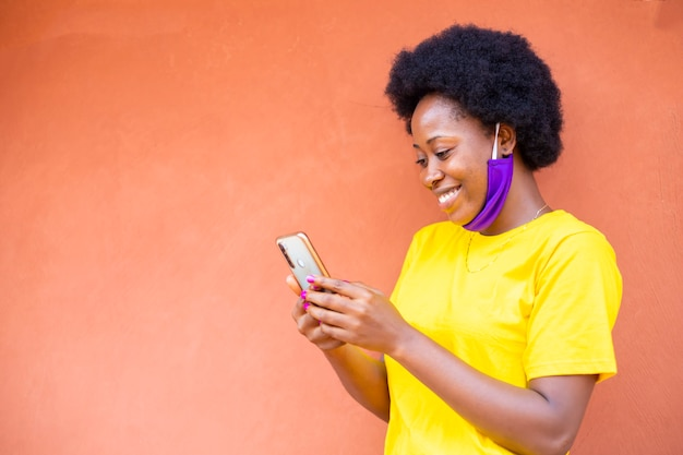 Zwarte afrikaanse vrouw voelt zich opgewonden na het ontvangen van goed nieuws van haar mobiele telefoon