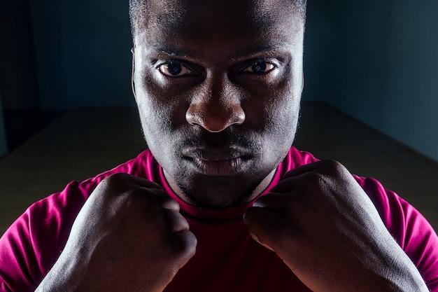 Zwarte afro-amerikaanse atletische man die op loopbanden loopt en oefeningen doet op spiergroepen, duw omhoog vanaf de bankgymnastiek op zwarte achtergrond