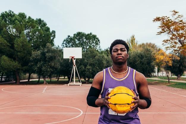 Zwarte afro-amerikaanse jongen basketbal spelen met een gele bal op een rechtbank. gekleed met een paars mouwloos shirt
